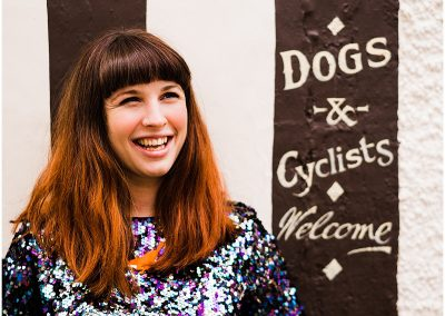 photo of florence fox standing in front of a wall which reads dogs and cyclists welcome - Ro Photographs