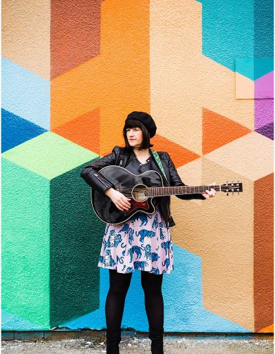 photo of Jodie from Shebeats standing with her guitar in front of multicoloured wall - Ro Photographs
