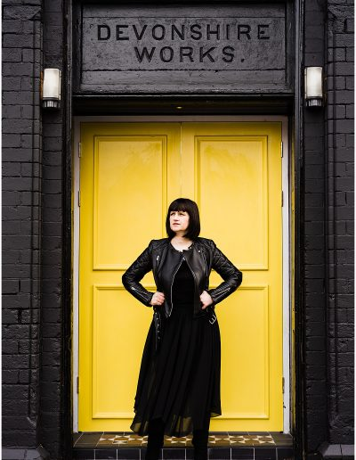 photo of Jodie from Shebeats standing otuside Devonshire Works yellow door- Ro Photographs